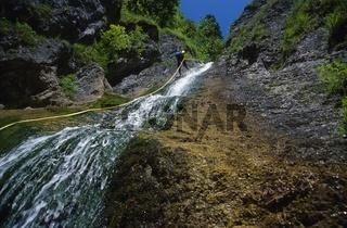 Ein Mann seilt sich beim Canyoning von dem Wasserfall 'Schleierfall' ab