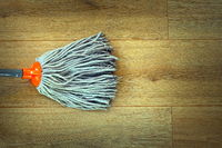 closeup of orange mop head cleaning on beige wooden parquet