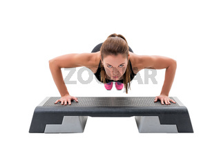 Young fitness trainer exercising on step platform