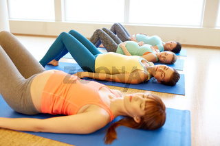pregnant women lying on mats in gym
