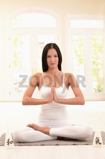 Pretty young woman doing yoga meditation