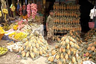 Verkäufer und Stand mit Ananas auf dem Markt in Galle