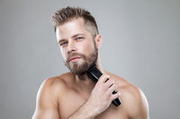 Handsome young bearded man trimming his beard with a trimmer