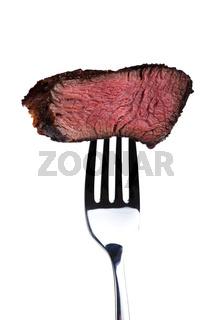 Stück eines gegrilltes Steak auf der Gabel