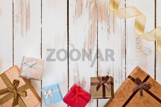 Christmas presents and golden ribbon over a rustic wooden table