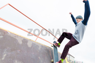 Teen skater in a hoodie sweatshirt and jeans slides over a railing on a skateboard in a skate park