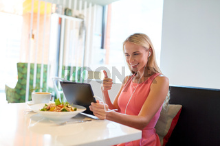 happy young woman with tablet pc at restaurant
