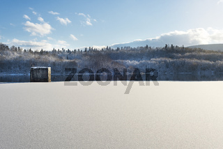 Winter landscape, lake with a dam in the foreground, against the forest and blue cloudy sky, beautiful nature, Western Ukraine