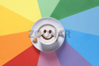 Coffee and smiley face on rainbow background