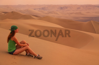 Young woman sitting on sand in a desert near Huacachina, Ica region, Peru.