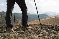 Close-up of male legs in trekking boots with sticks for Nordic walking against the background of rocks and distant Caucasian lands