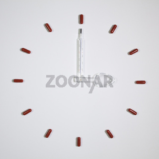 Clock of twelve pills, medical thermometer and plastic spoon