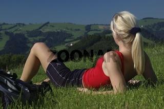 Blonde Frau (22) liegt in der Wiese und geniest nach einer Wanderung den sommerlichen Ausblick über die Voralben