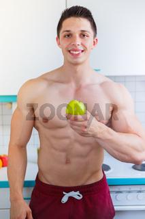 Gesunde Ernährung junger Bodybuilder Mann Essen Apfel Frucht Obst in der Küche Hochformat