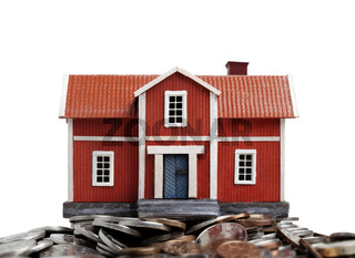 Model of house on pile of coins