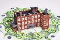 Fabrikgebäude und Geldscheine