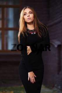 Sad young fashion woman in black dress on night city street