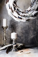 Christmas wreath of feathers with candlesticks on a gray background