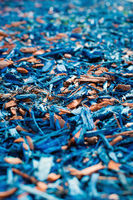 Textured background decorative colored sawdust for finishing flowerbeds in the winter season in outlook. Blue and maroon sawdust