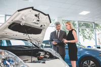 Auto dealer showing motor of electric car to young woman.