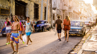 Streetscene of Cuban people walking in old Havana at sunset