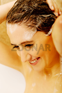 Young happy woman washing hair in bath