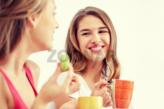 happy young women drinking tea with sweets at home