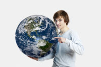 Handsome young man pointing and holding the planet earth on its hands