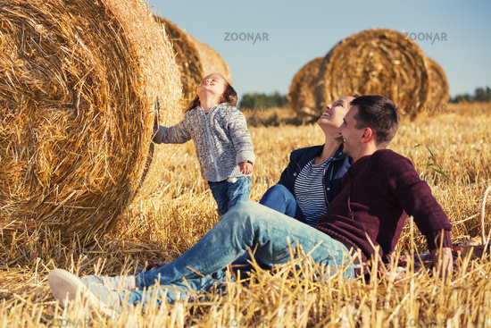 Happy young family with 2 year old girl next to hay bales in harvested field
