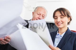 Geschäftsfrau und Senior blicken auf Dokumente