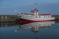 Ein weißes Schiff spiegelt sich am Abend im stllen Wasser an der Pier.