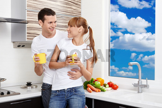 Young embracing couple with yellow mugs at kitchen
