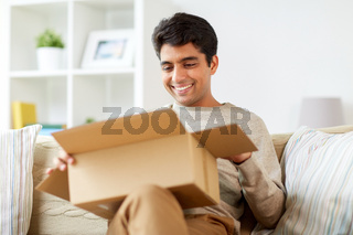 happy man opening parcel box at home