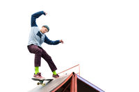 Teen skater in a hoodie sweatshirt and jeans slides over a ramp on a skateboard isolated on white
