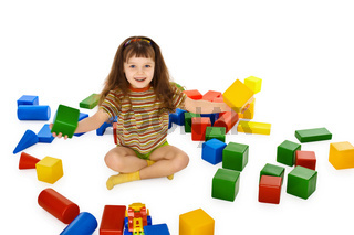 Little girl playing with color cubes on floor