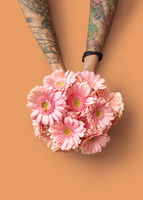 Hands of a woman with a tattoo hold a beautiful bouquet with pink gerberas on an orange background
