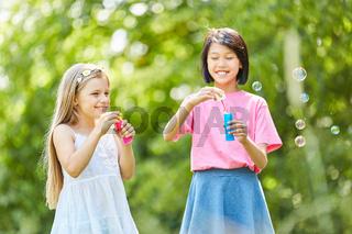 Zwei Mädchen machen Seifenblasen