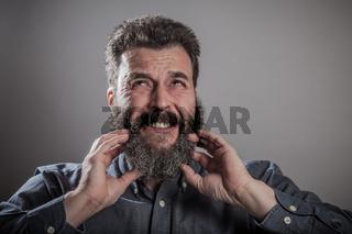 Scratching huge beard portrait, mature adult Caucasian man