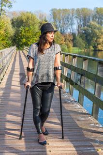 Woman with crutches walking on bridge