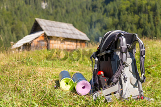 Backpack and yoga mats on mountain meadow.
