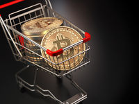 Bitcoin BTC coins in the shopping cart on black background. Cryptocurrency market concept.