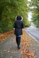 unrecognizable woman wearing winter coat and boots walking down the street