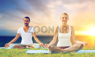happy couple making yoga and meditating outdoors