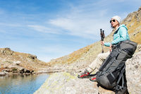 A tourist girl wearing sunglasses down jacket and hat with a backpack and mountain equipment with handles for tracking in her hands is sitting on high mountain lake