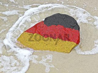 Flagge von Deutschland auf einem Findling am Ostseestrand
