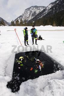Eistaucher sitzen am Eisloch, Scuba diver sitting at hole of frozen lake, Plansee, Oesterreich, Austria