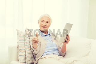 senior woman with tablet pc showing thumbs up