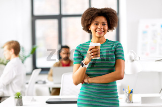 smiling african woman drinking coffee at office