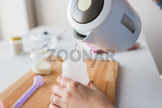 hands with kettle and bottle making baby milk