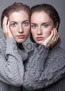 Two young women in gray sweaters on grey background. Beautiful girls stretching hands forward in embrace. Girls with hands near face.